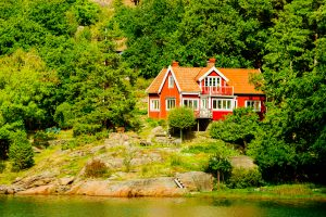 Askeron, Sweden - September 9, 2016: Environmental documentary of seaside home in woodland slope down to water.