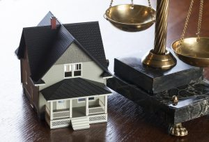 House and Scales of Justice on wood table. Concept mortgage, foreclosure, refinance