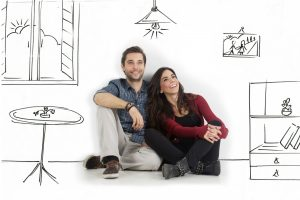 Young couple sitting on floor looking up while dreaming their new home and furnishing.