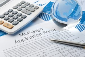 """Mortgage application form with a calculator, pen and globe"""