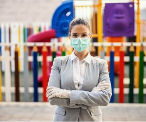 young-woman-with-protective-mask-and-gloves-standing-in-front-of-picture-id1217769992-1